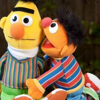 A puppet whispering into another puppets ear