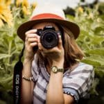Image of a girl holding a camera up in front of her face taking a photo