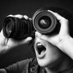 Image of man holding two camera lens to his eyes