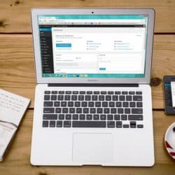 Turned-on Macbook Air Beside Black Iphone 4, Cup of Tea, and Notebook on Brown Wooden Surface